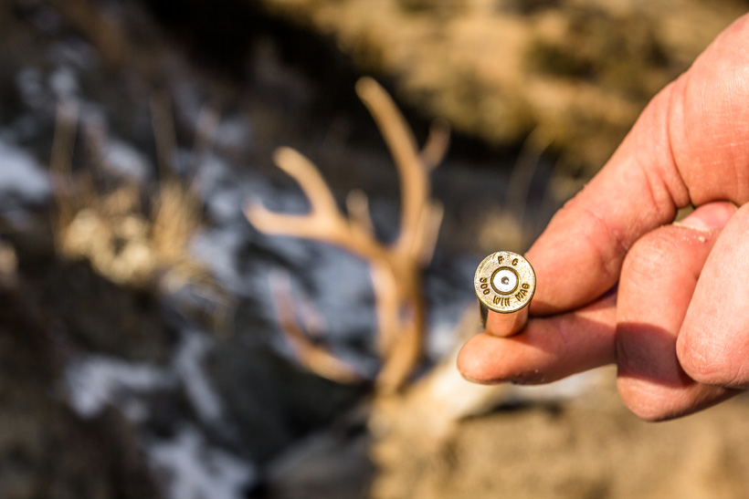 Bryce Miller holding rifle cartridge after taking mule deer