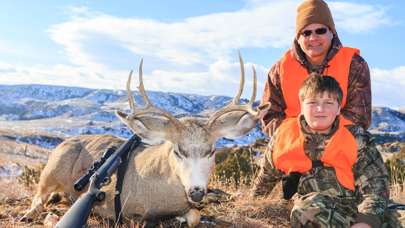 Youth hunter with his first mule deer buck