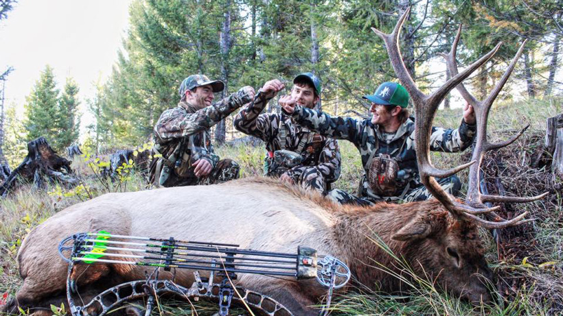 Friends fist pounding after successful elk hunt
