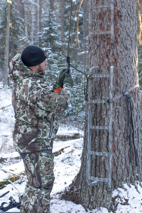 Jon Gabrio setting up his safety harness on treestand