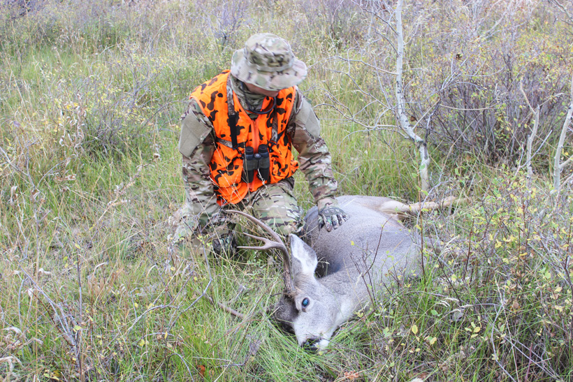 Mark giving respect after shooting mule deer buck