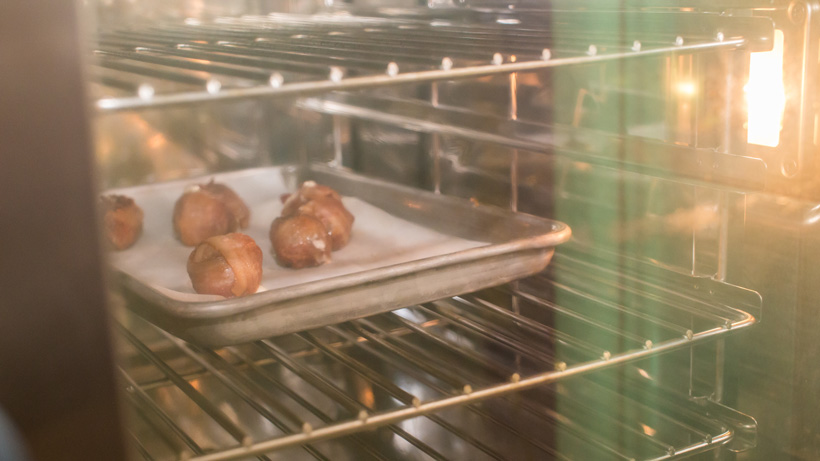 Place elk meatballs wrapped in bacon in oven