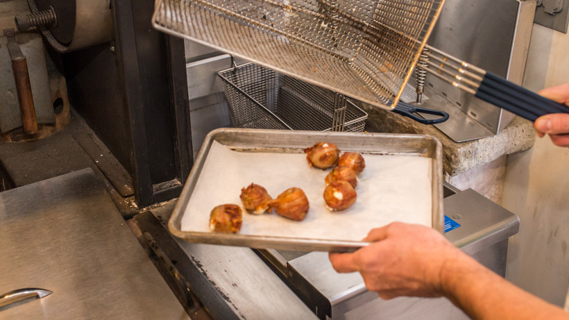 Removing elk meatballs wrapped in bacon from fryer
