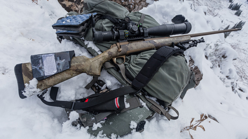 Shooting rifle off backpack in snow