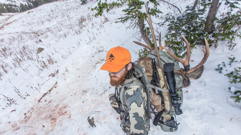 Solo packing out deer meat in backpack