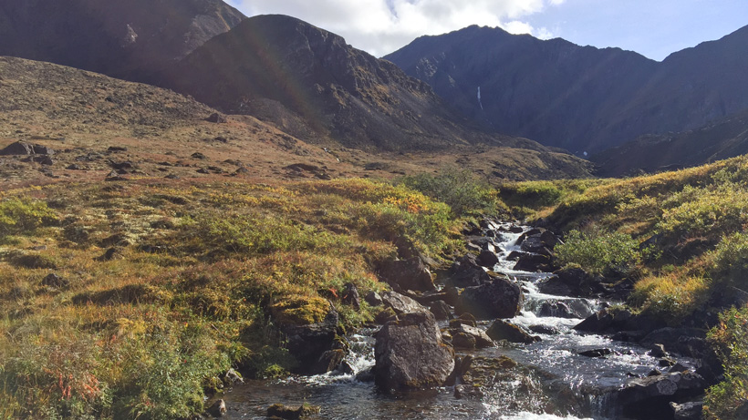 Stream with mountain scenery while hunting dall sheep