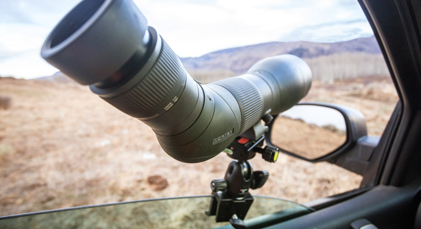 Summer mule deer scouting with spotting scope from truck