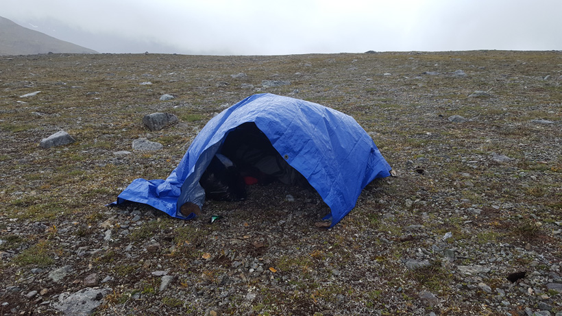 Tarp to protect gear during rainstorm
