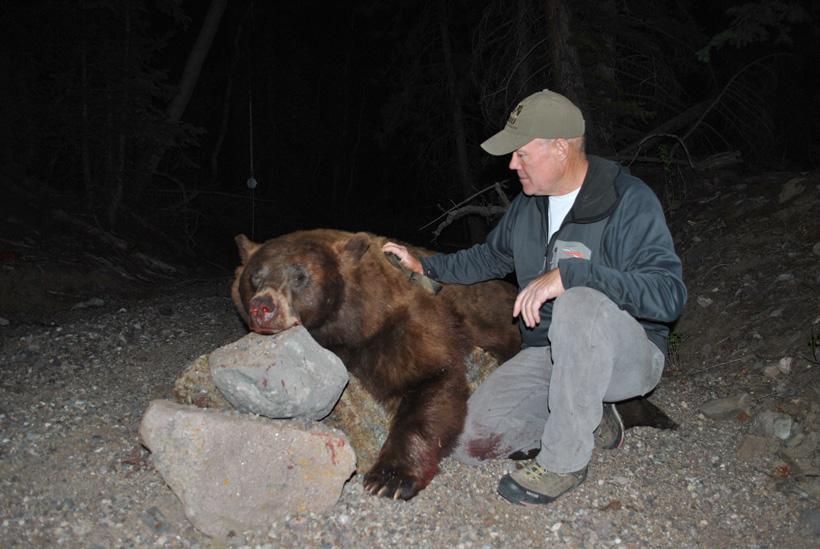 Todd knealing next to his black bear