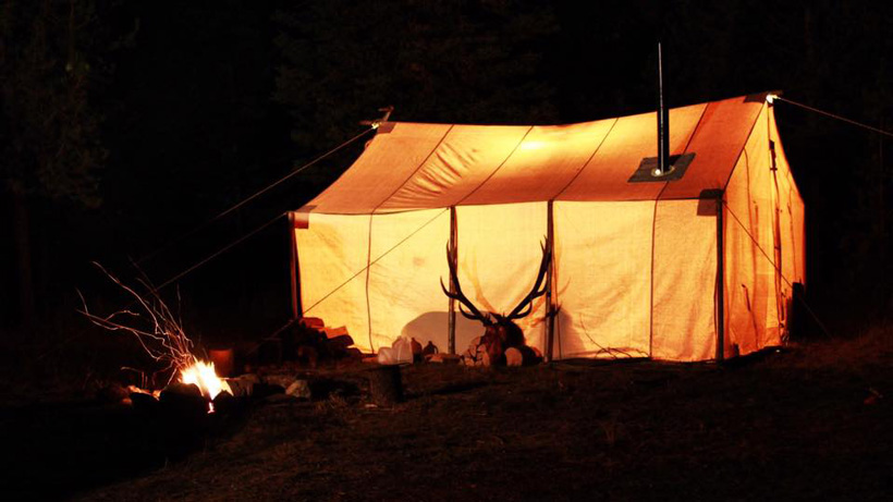 Wall tent at night with elk antlers